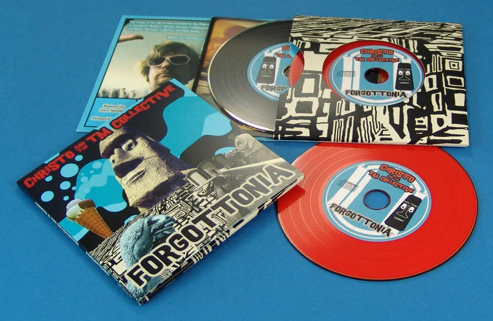 A double vinyl CD four page wallet with a black vinyl DVD and red vinyl CD, plus a booklet