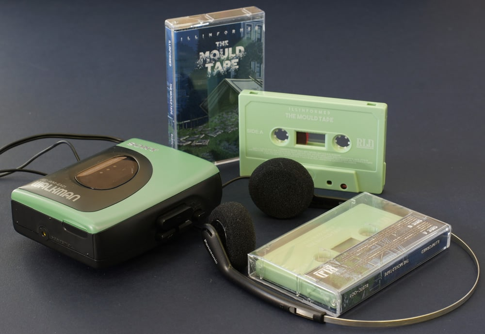 A set of sage green cassettes with white on-body printing